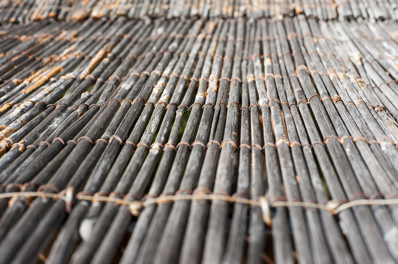 Close up low angle view on cane floor mat with strings holding it together and pattern of converging lines and selective focus