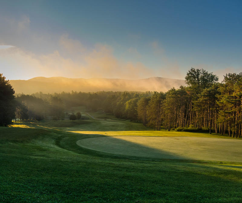 <p>Golf course in the morning with mist clearing.</p>