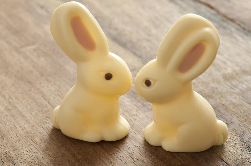 Close-up of two Easter bunny candies of white chocolate sitting on wooden table close, as if kissing