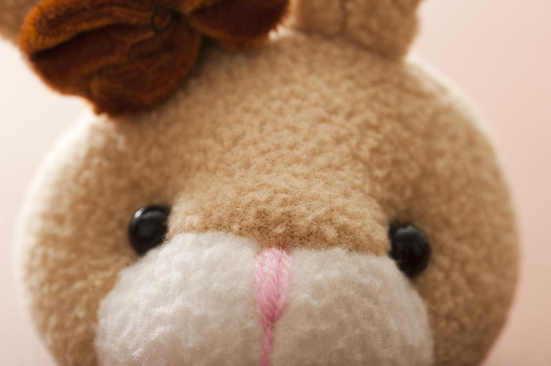Cute little face of a soft fluffy toy Easter bunny staring at the viewer in a close up cropped view