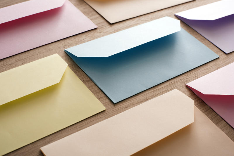 Rows of colorful paper blank Easter cards envelopes over wooden table, invitation concept background