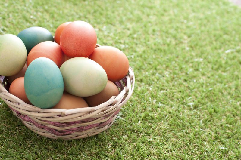 Rustic woven wicker basket of traditional dyed Easter Eggs on a green lawn with copy space alongside