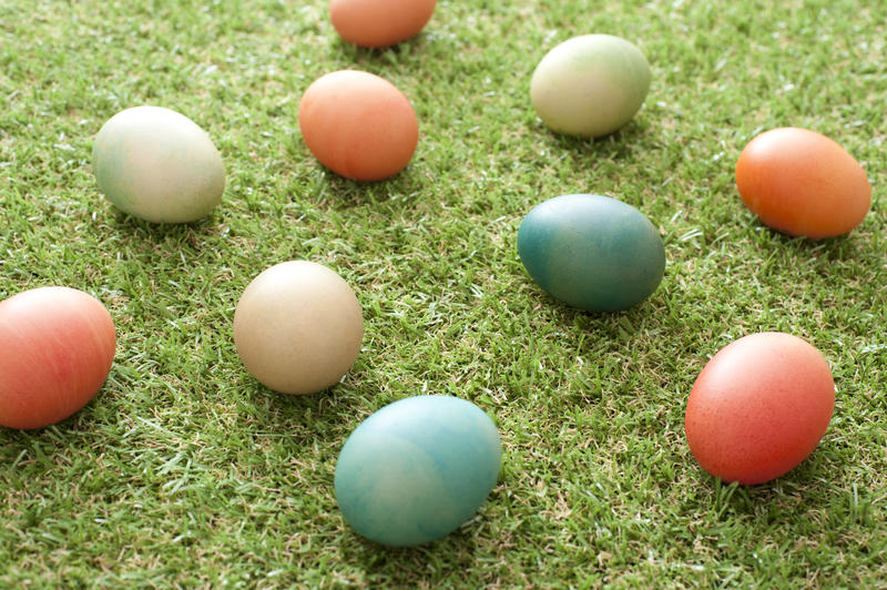 Scattered homemade dyed Easter eggs in pretty pastel colors on neat green spring grass viewed at an oblique angle for a holiday background
