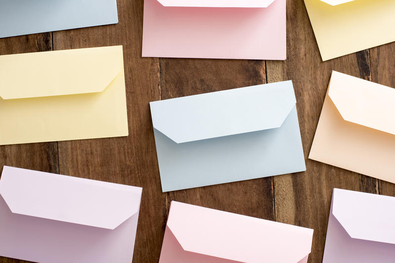 Still life of colored Easter envelopes lying face down with open flaps on a wooden background viewed from overhead
