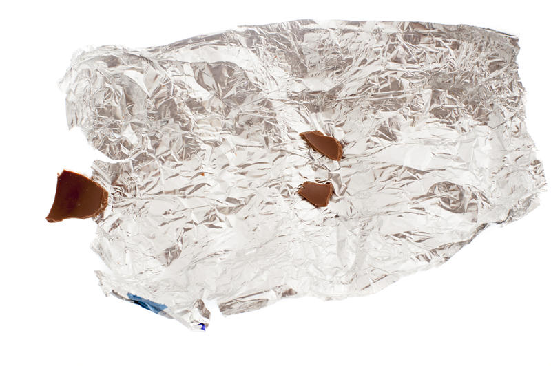 Close up view of crumpled foil with remains of chocolate pieces of eaten Easter Bunny candy isolated on white background