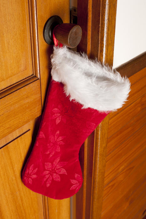 Colorful red Christmas stocking hanging on the handle of a wooden door waiting for the arrival of Santa to fill it with gifts