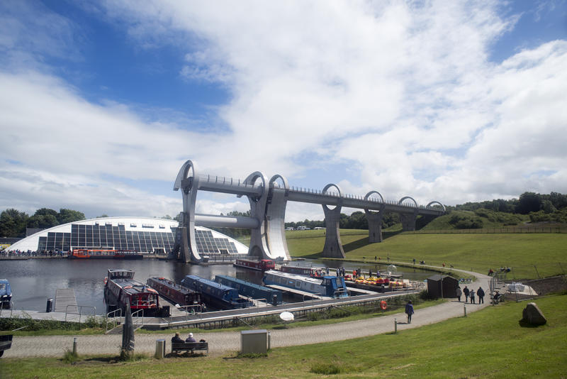 Wide angle view of path, docked small ships and people near harbor at Falkirk Wheel boat lift in Scotland
