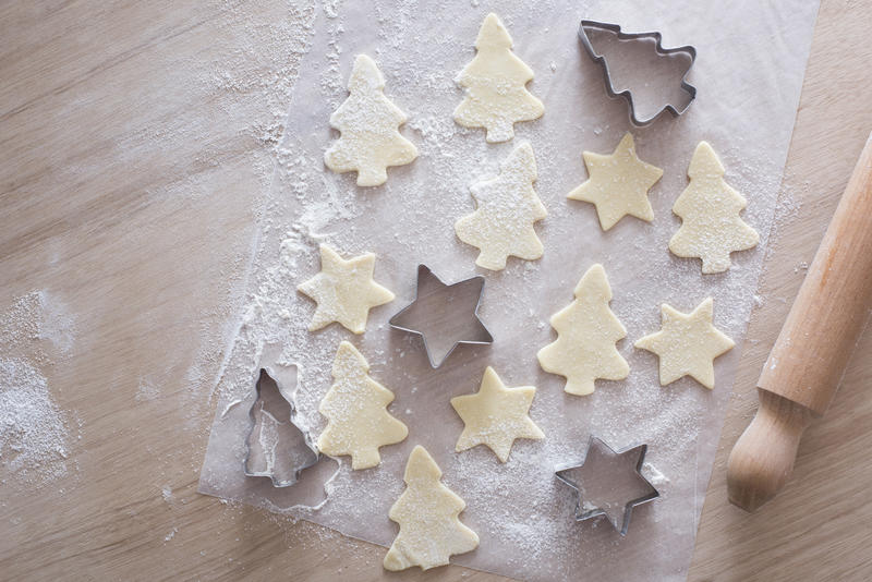 Overhead view of unbaked tree and star shaped cookies beside tin cutters and rolling pin