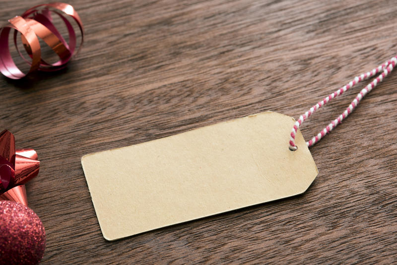 Blank Christmas gift tag with red themed decorations forming a side border on wood with copy space for your greeting or message