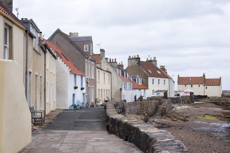 Rows of two story houses and narrow lane during low tide at Pittenweem coast in Scotland