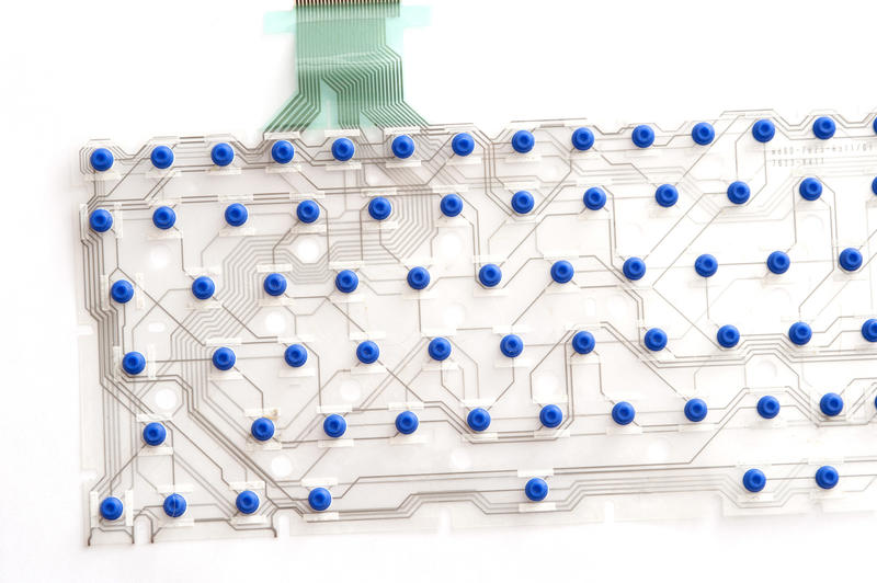 Flexible circuit layout of keyboard with blue pins on transparent film isolated on white background