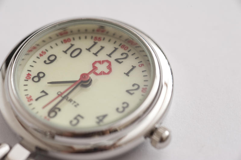 Close up on the round silver metal dial of a nurses watch with a red cross on the face in a time keeping and precision concept