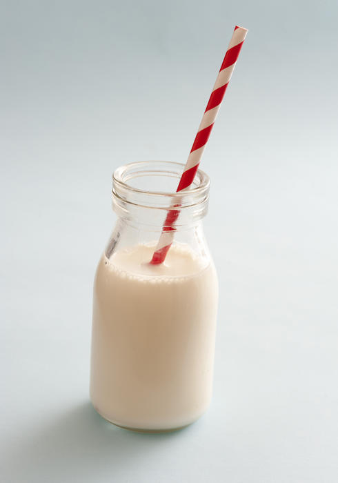 13003   Small glass bottle full of milk with a straw