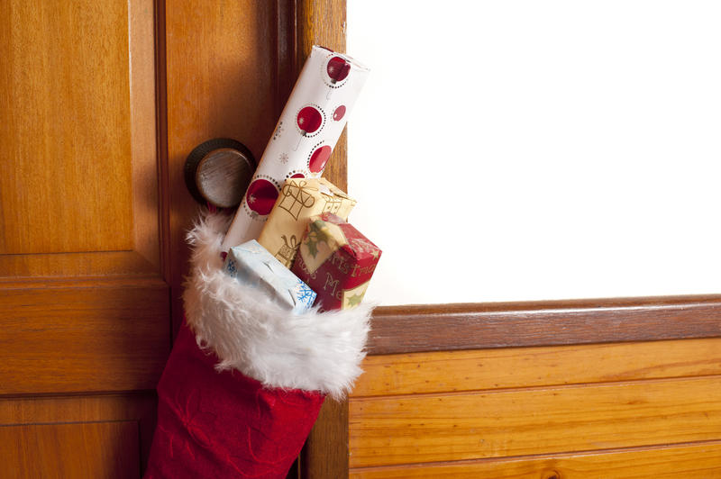 Red Christmas stocking filled with small gifts hanging from a wooden door to celebrate the holiday season, copy space for your greeting