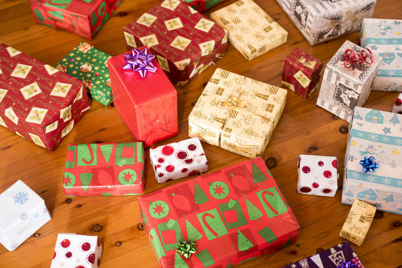 A close up of various, unopened Christmas presents on timber floor.