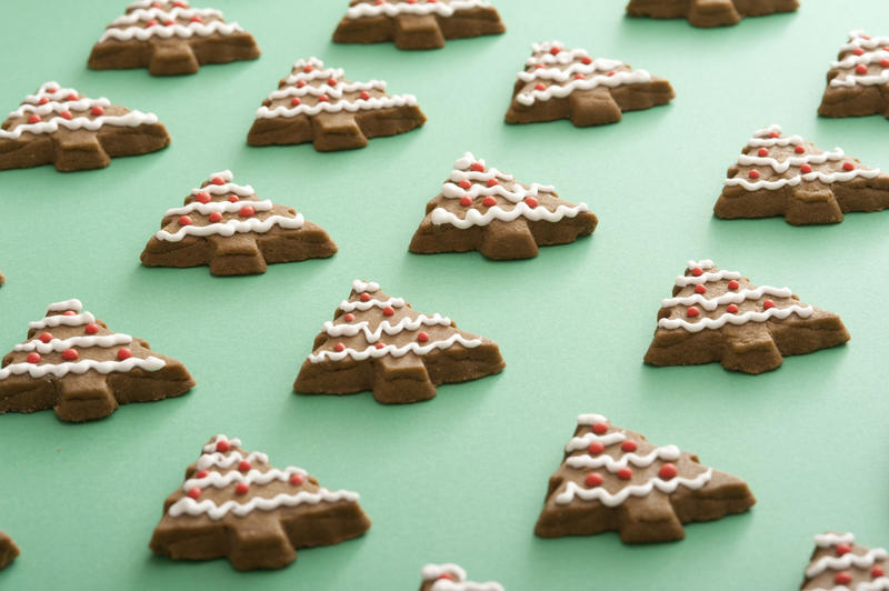 Green cookie sheet laid with rows of tree shaped goodies with white and red frosting