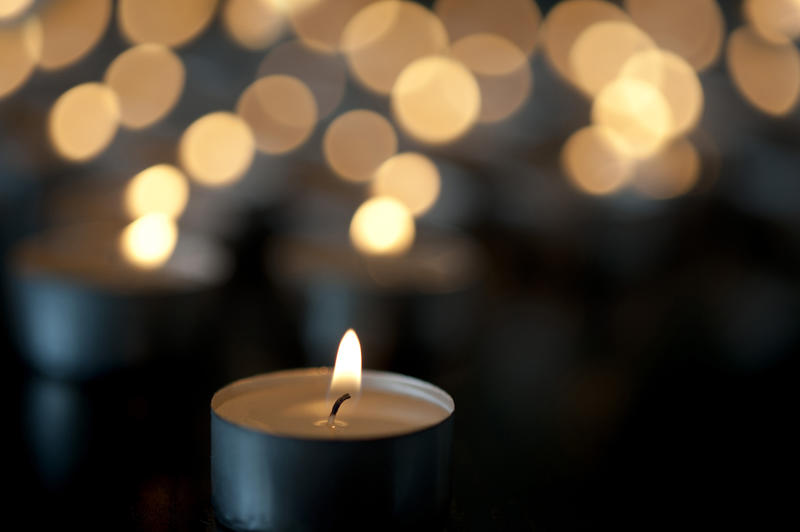 Close-up image of little candle tealight burning in the dark with many glimmering candles blurred in bokeh effect background