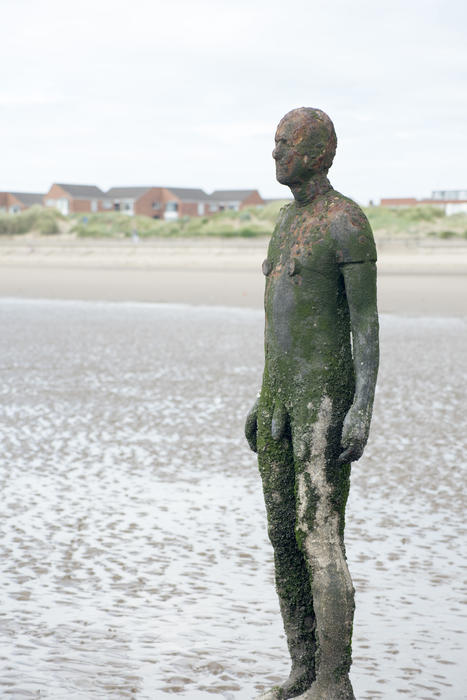 Cast iron figure from Another Place by Anton Gormley on Crosby Beach, UK