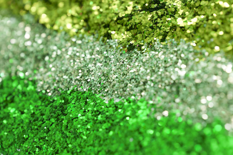 a background with three colours of green glitter in rows