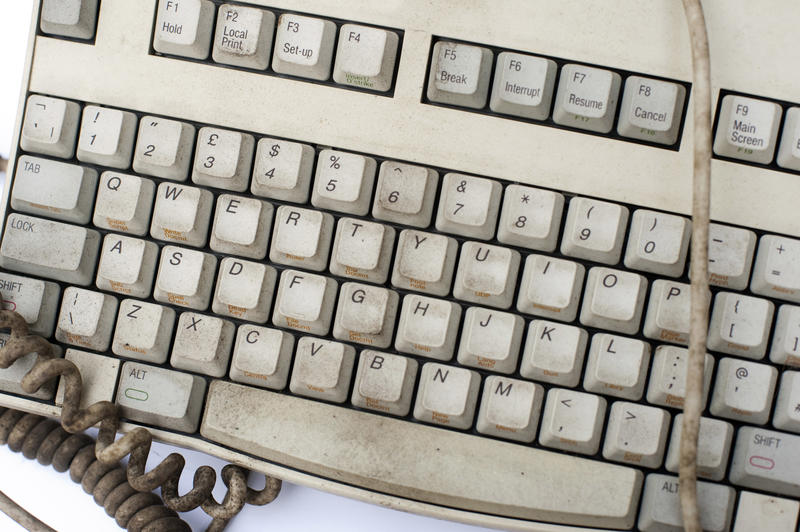 Old dirty grungy white computer keyboard with cords and cables viewed close up from above