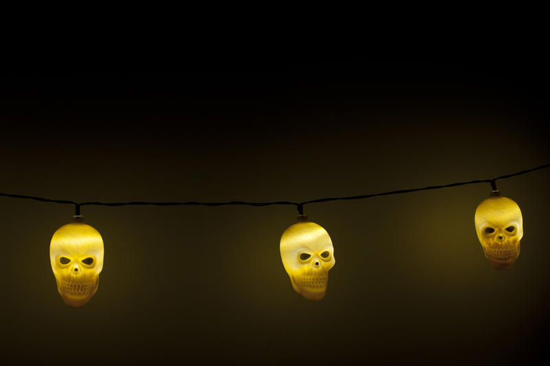 Close Up of String Glowing Halloween Skull Lights Suspended in Eerie Dark Room Against Plain Wall with Copy Space