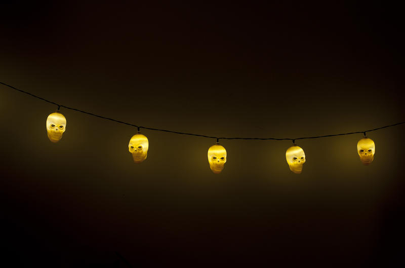 String of ghostly glowing yellow Halloween skull lights against a black background with copy space
