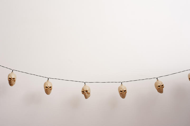 String of creepy ghoulish unlit Halloween skull lights over a white background with copy space for your festive message