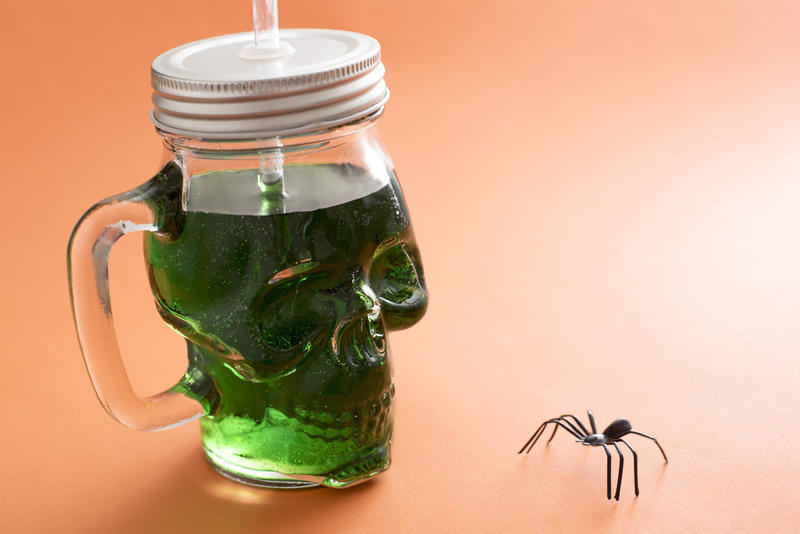 Spooky green Halloween drink in a skull shaped Mason jar with lid facing a creepy spider on an orange background with copy space