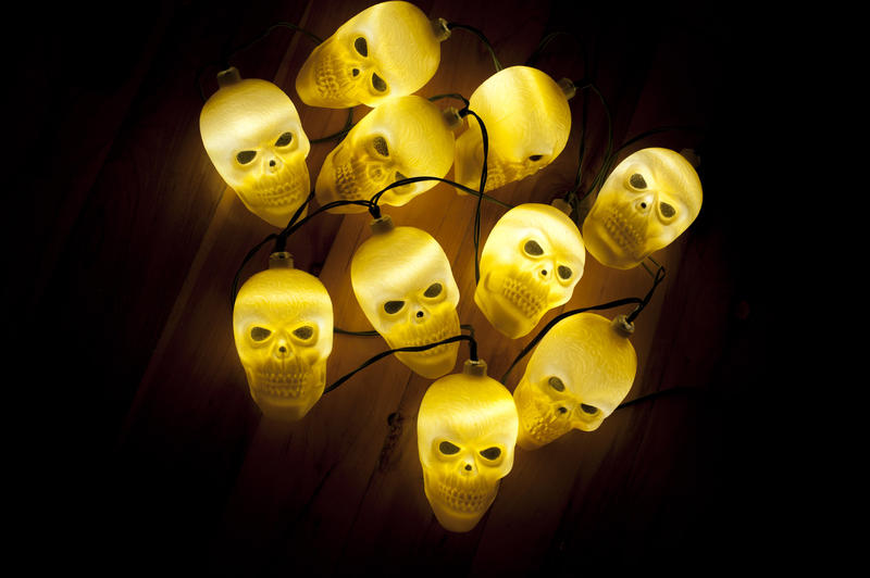 Cluster of ghostly glowing yellow skull lights centered on a dark background to celebrate Halloween