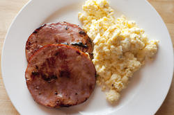 12267   Fried ham slices beside scrambled eggs in plate