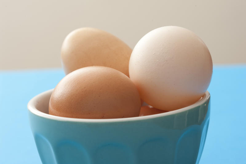 Fresh whole raw brown and white hens eggs in a blue ceramic bowl on a blue kitchen table in a close up view