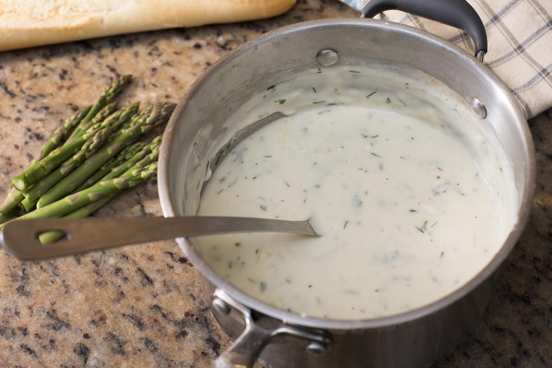 Stainless steel pot with herbed white sauce and spoon beside a small bunch of asparagus