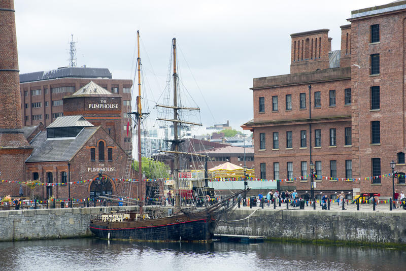 Sailboat or tall ship moored at the quay on the Liverpool waterfront with tourists and historical buildings behind