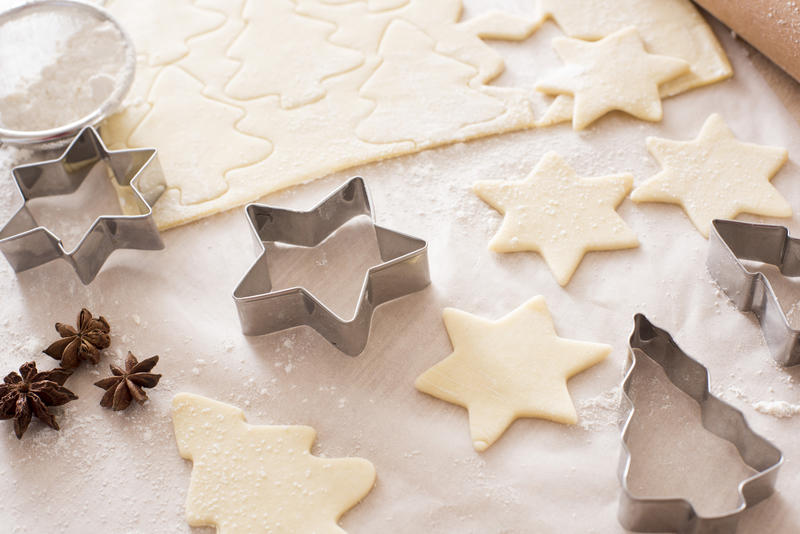 Making star and tree-shaped Christmas cookies at home with meal cookie cutters and star anise spice with cut out uncooked pastry on floured oven paper