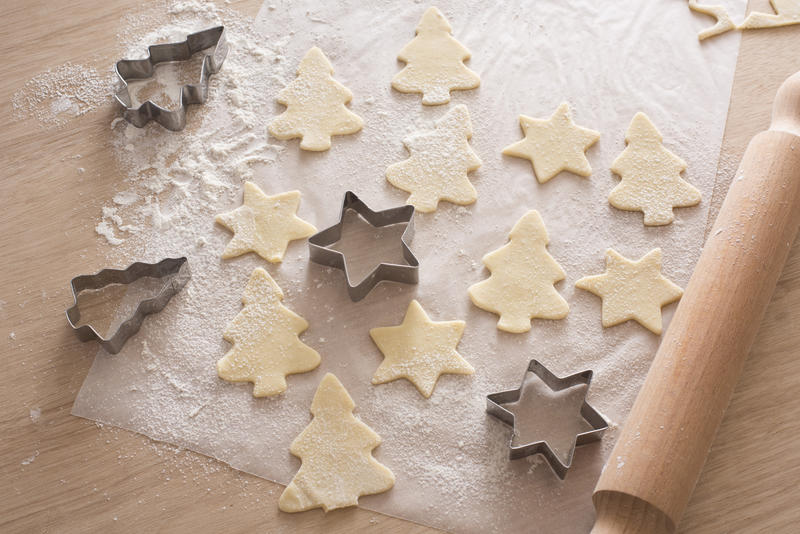 Cooking festive homemade Christmas biscuits with cut out pastry shapes alongside a star and tree shaped cookie cutter and wooden rolling pin on a kitchen counter