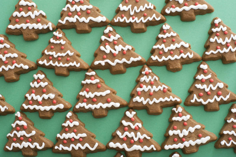 Iced gingerbread cookie background pattern with delicious traditional Christmas tree shaped biscuits on green in a full frame view