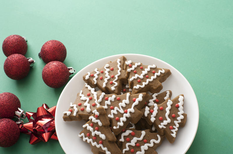 Iced gingerbread Xmas tree cookies served on a plate alongside festive red Christmas baubles and bows on green with copy space for your greeting
