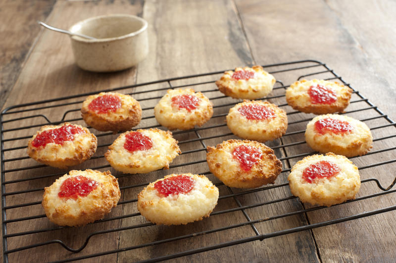 Batch of delicious jam drop biscuits filled with strawberry jam cooling on a wire rack in the kitchen on a wooden counter