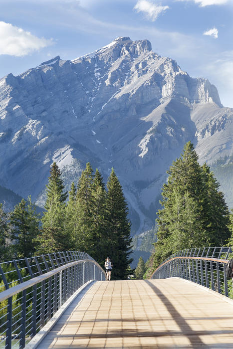 <p>A female jogger runs over a wooden bridge in Banff, Canada with the Rocky Mountains in the background</p>