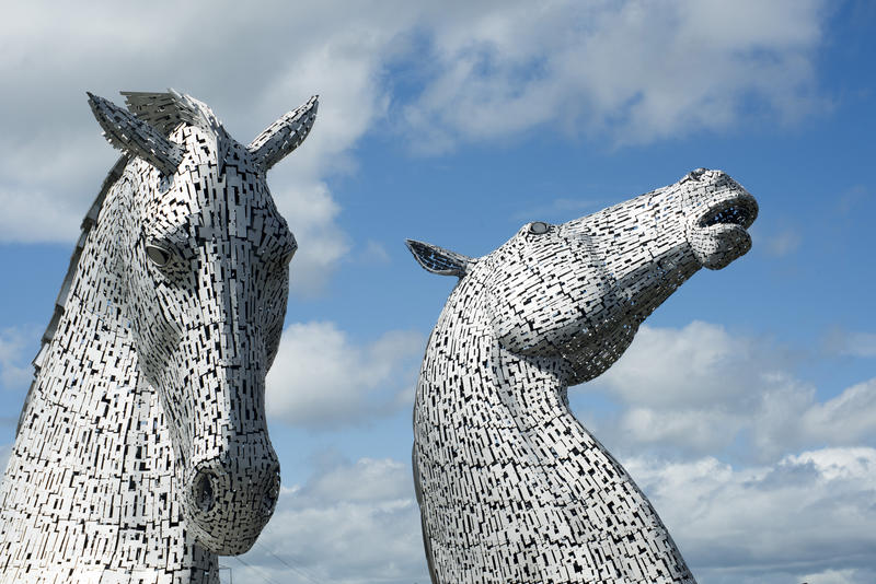 The Kelpies, Falkirk, Scotland against a blue sky a sculpture of two horses heads commemorating their role in industry
