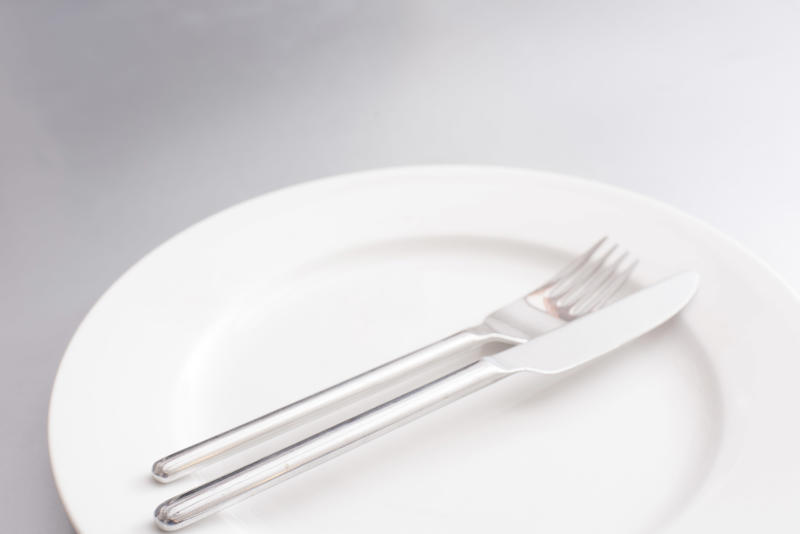 Empty clean generic white plate and silver cutlery with a knife and fork neatly arranged in the centre in a cropped view