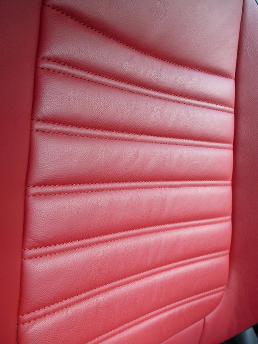 Red leather car seat texture with a ridged design for comport in an oblique angle view