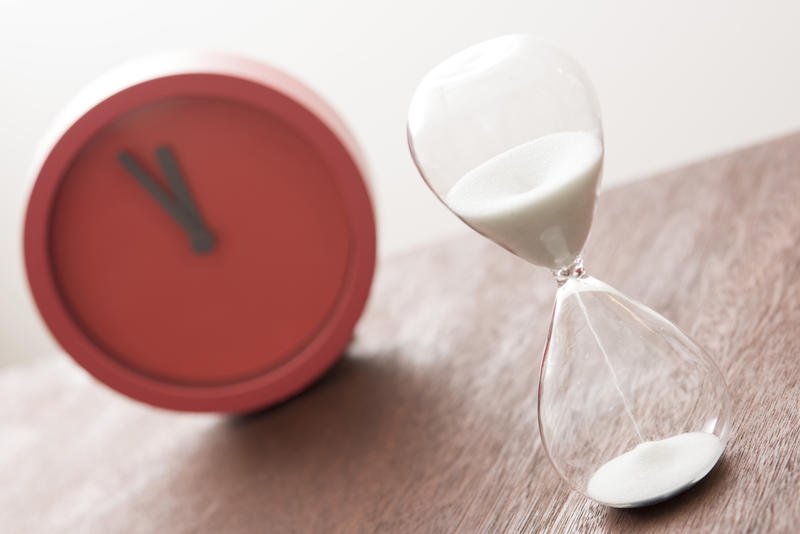Counting down cooking time in the kitchen with a glass egg timer or modern red timer clock in a tilted angle view with focus to the hourglass