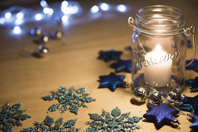 Burning candle in a glass jar surrounded by Christmas ornaments on a wooden table with copy space and background bokeh of sparkling party lights