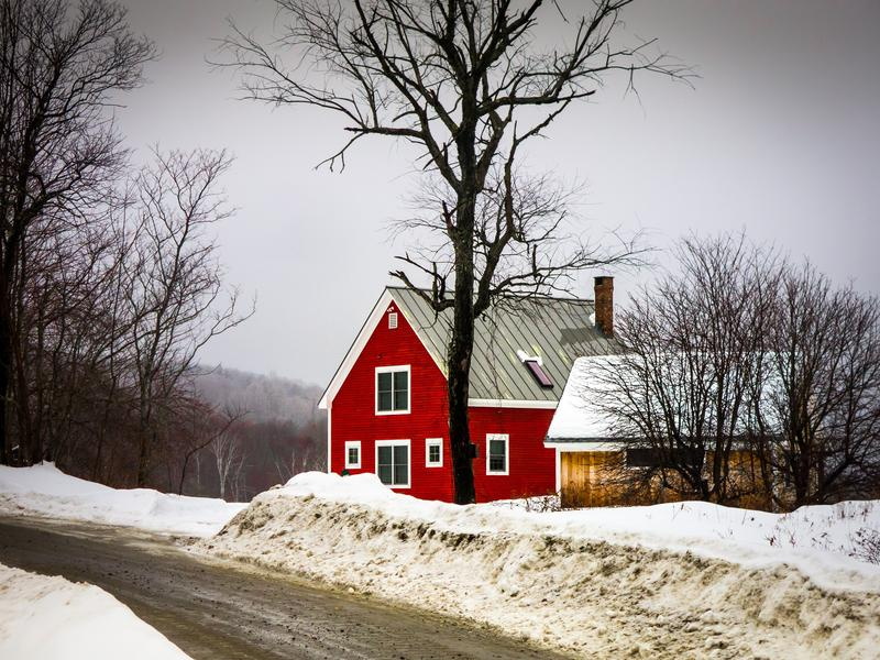 <p>Little red Christmas House and barn in the winter by the road with snow and naked trees, rural Vermont.</p>