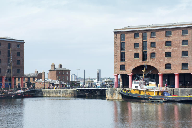 Calm waters and yellow tugboat at Liverpool Albert Dock in the United Kingdom, Europe
