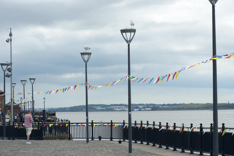 Liverpool, UK, Mersey waterfront on a cloudy day with festive bunting strung between the lampposts lining the promenade overlooking a calm ocean