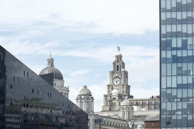 Modern and historic architecture, Liverpool, UK with a view past a skyscraper to the clock tower of the Liverpool building in the distance