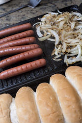 12761   Hot dogs being prepared on grill with onions