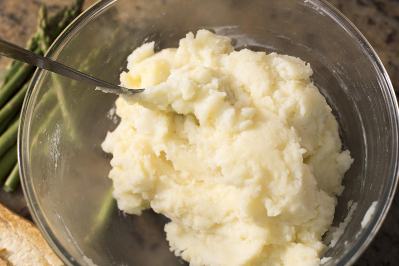 Buttered mashed potatoes in glass bowl with spoon set on a granite counter beside asparagus bunch